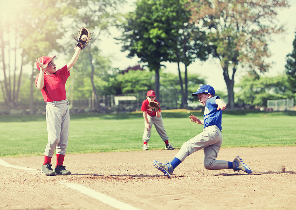 Boy gets an out at third while playing baseball at a sports complex