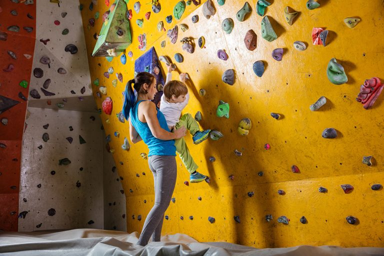Climbing instructor helps a boy at a sports complex