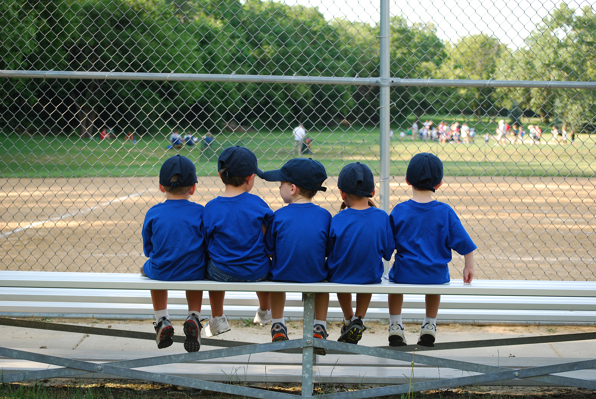 Young baseball team watching a game at a recreation center