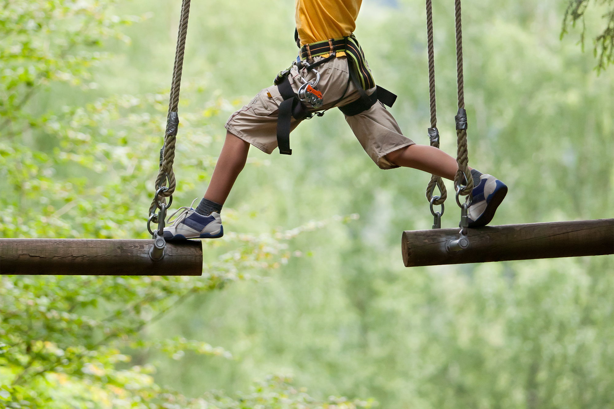 Boy traverses ropes course on the grounds of a Sports Facilities Advisory client