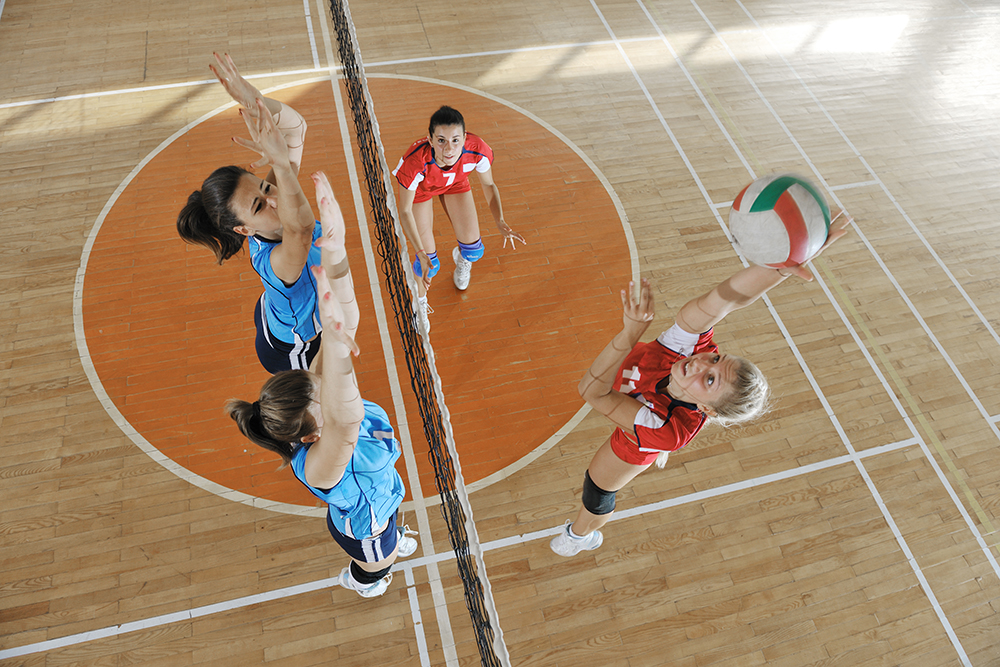 Women play indoor volleyball at a sports complex