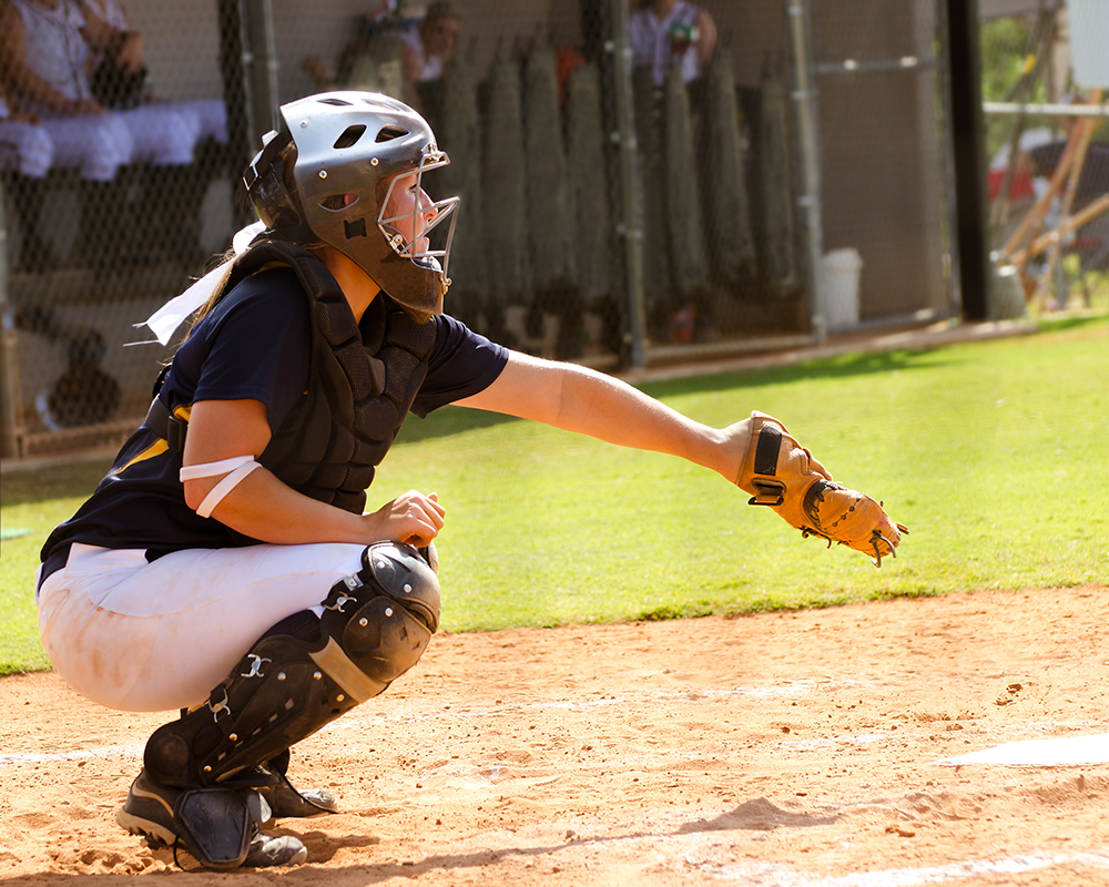 Female catcher plays ball at a sports complex