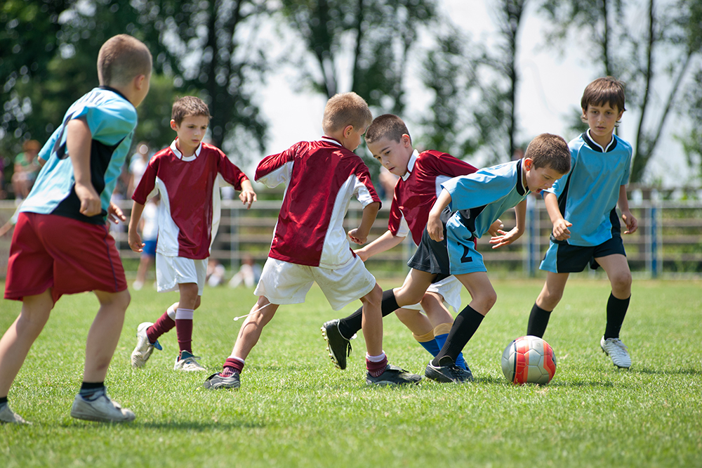 two teams of boy compete in a soccer game at a sports complex