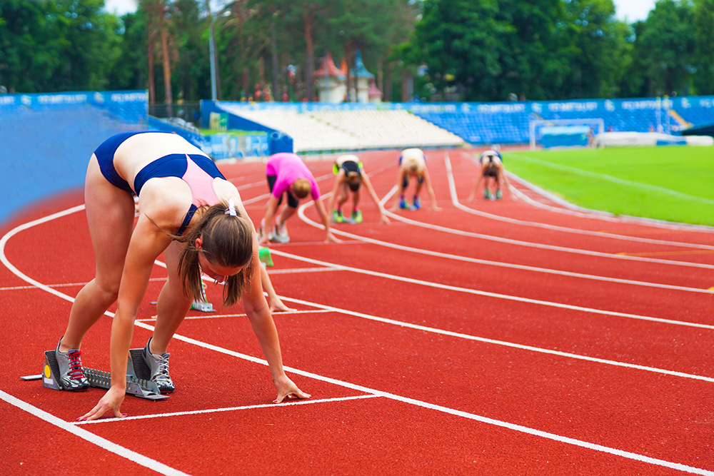 Female track runners compete at sports complex