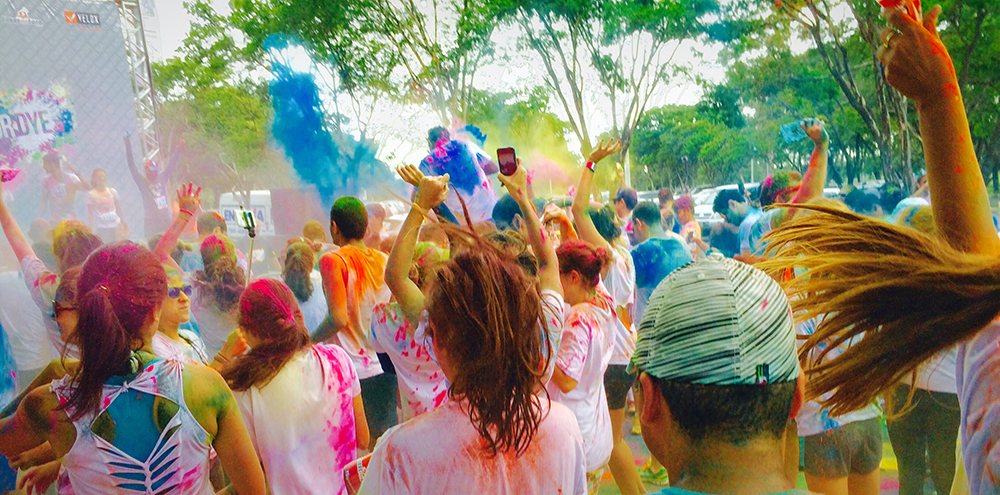 Runners cheer at the finish line of a color run at a sports complex