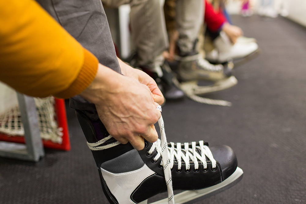 person ties ice skates at a sports complex