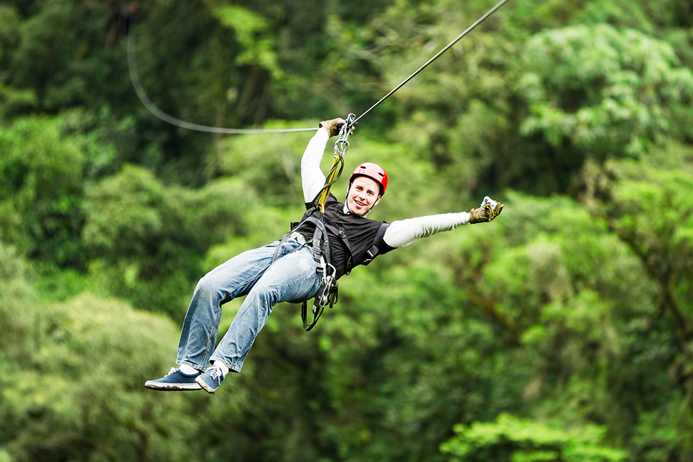 Man rides a zipline at Empower Adventures, a client of Sports Facilities Advisory