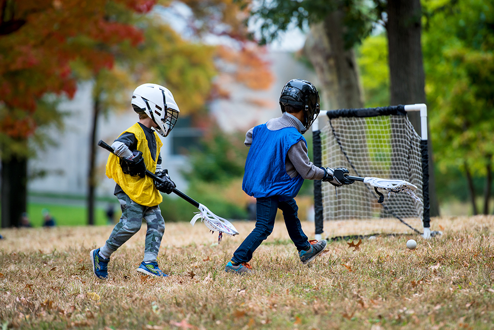 Young boys play lacrosse in autumn at their sports complex