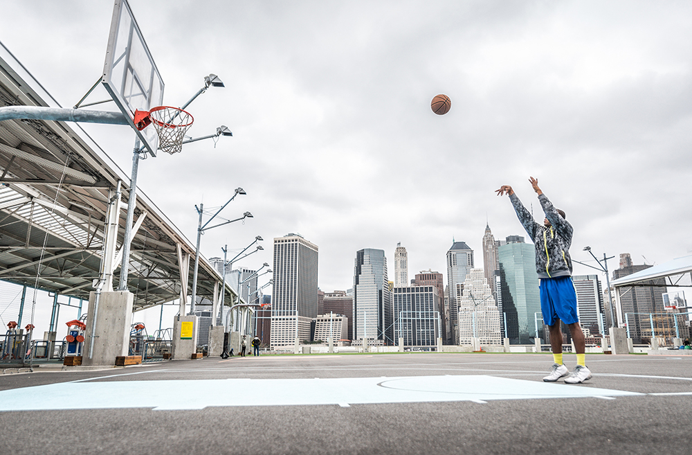 man practices free throws on outdoor courts of his recreation center