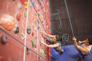 Girl climbing rock wall in recreation center