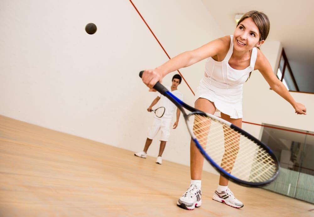 A Woman Plays Squash at a Recreation Center