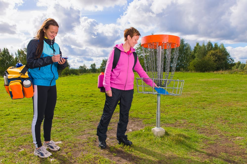 Women playing disc golf at outdoor sports complex