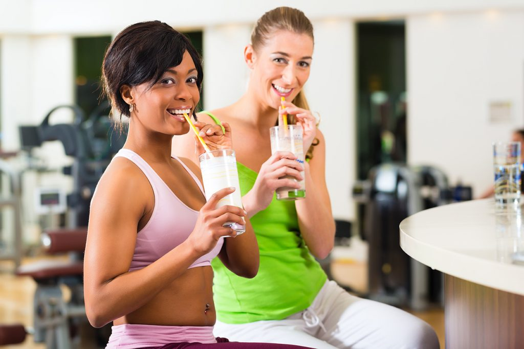 Healthy Women with Protein Shakes at Sports Complex