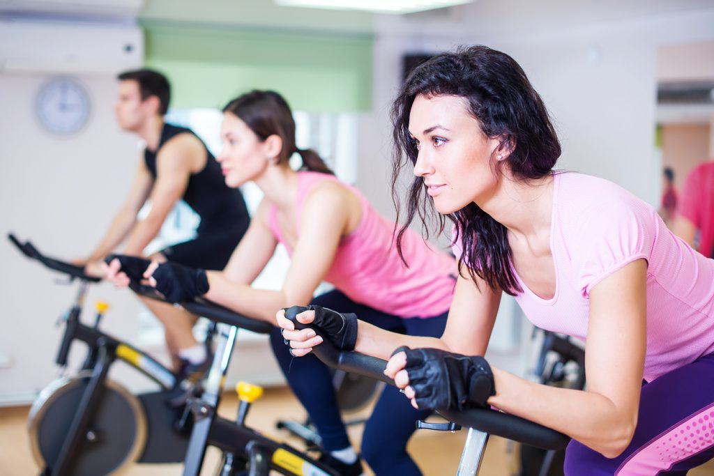 Three people at group indoor cycling class at sports complex