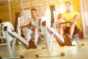 man and woman on rowing machines at a sports complex