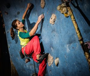 Woman rock climbing at recreation center