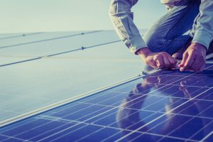 Engineer installing solar panel after feasibility study