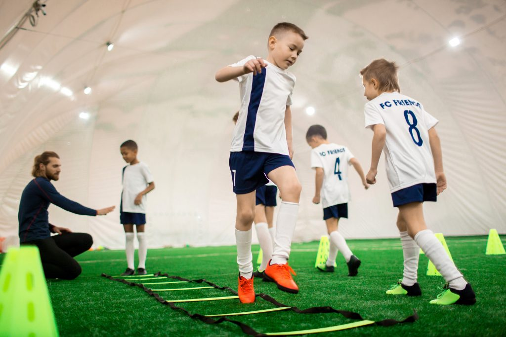 Kids participating in a soccer practice at an indoor sports facility