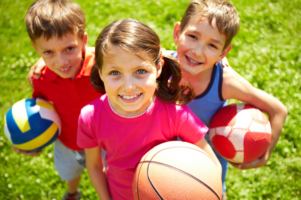 Kids holding different balls at sports complex.