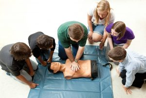 Group of people doing CPR training.