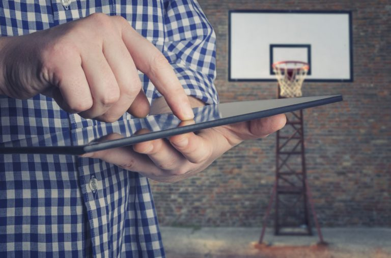 Coach using tablet on basketball court