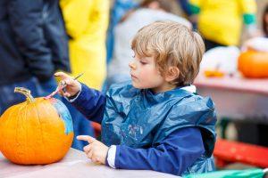 Child painting a pumpkin