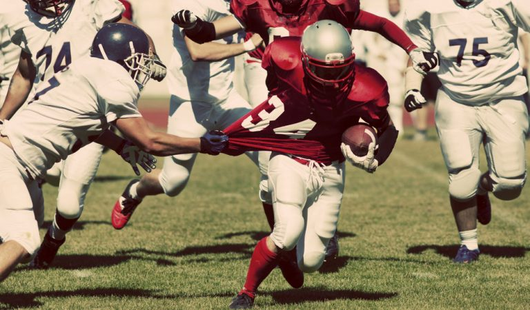 Young ball carrier avoiding a tackle