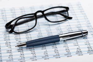 Financial data sheet with glasses and pen.