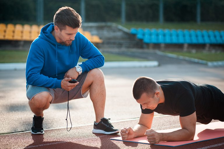 Fitness coach working with client