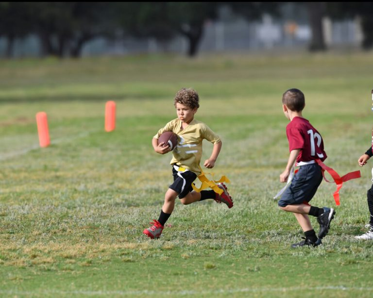 Flag football player running past defender with the ball.