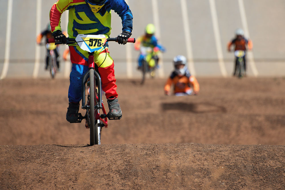 BMX Riders racing over dirt track