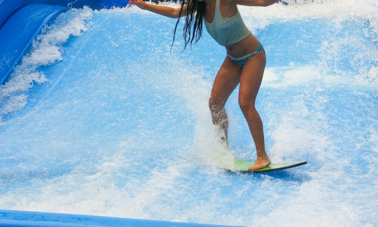 Young woman surfing in indoor wave pool
