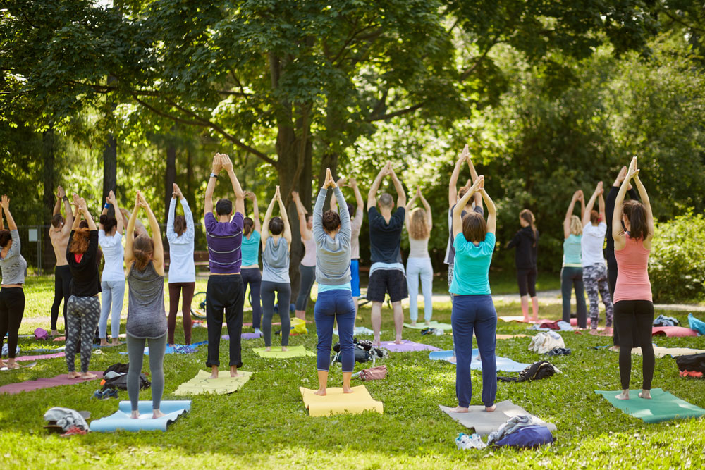 Group of people practicing yoga in a public park