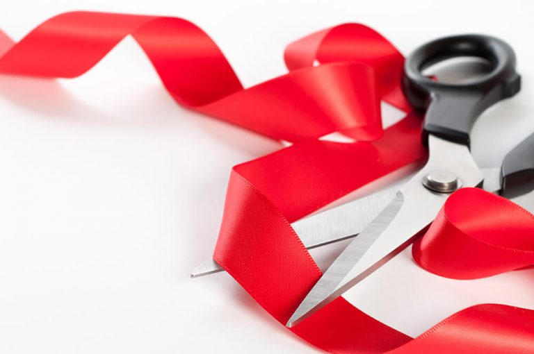 Cutting a red ribbon.