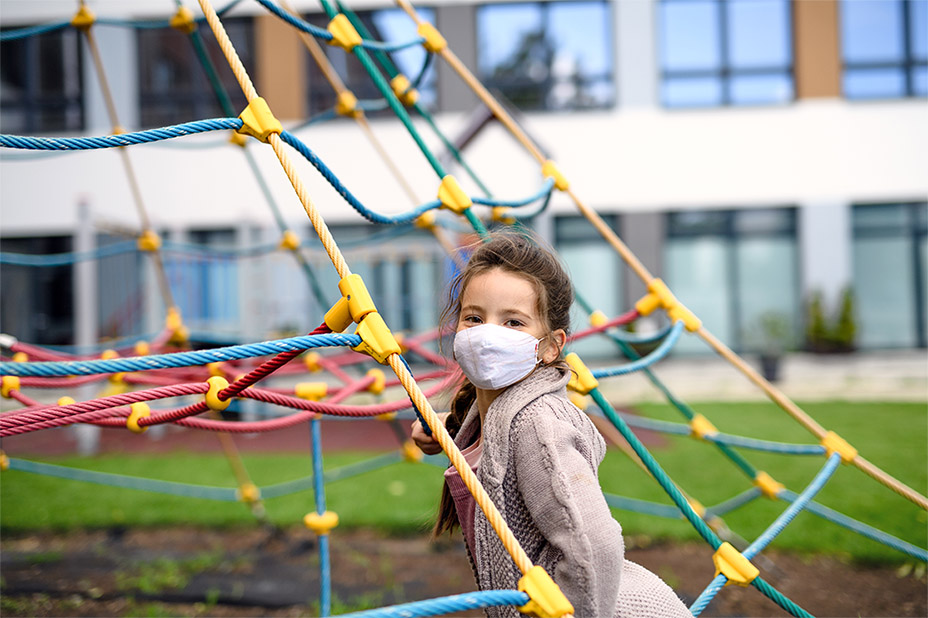 Portrait of happy child with face mask on playground after covid-19 lockdown.